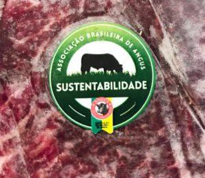 carne bovina com selo redondo em verde com um boi em preto pastando e o selo de certificação da associação brasileira de produtores de angus