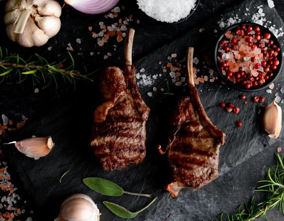 Corte de cordeiro chamado carre francês assado em fundo preto com temperos alho, pimenta, sal grosso rosa e folhas de louro na mesa
