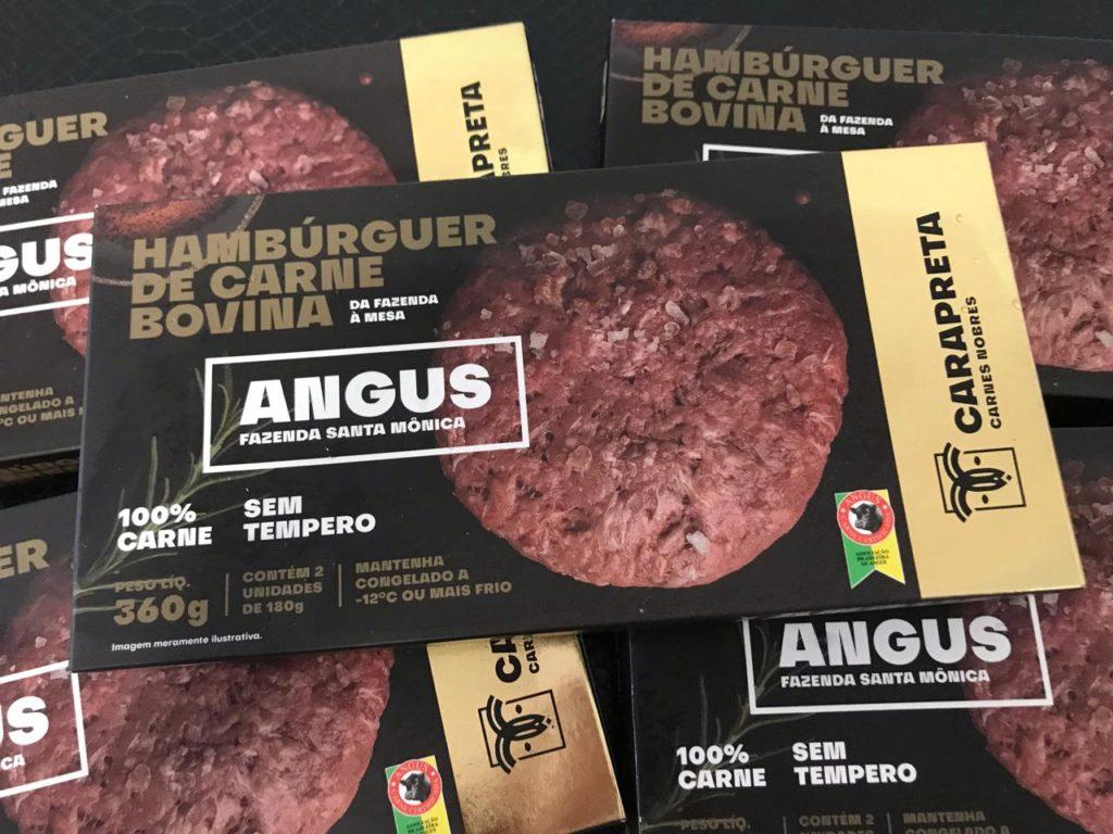 Caixa preta com detalhes em dourado escrito Hamburguer de carne bovina Angus com as informações: 2 unidades de 180 gramas, sem tempero e com selo de certificação