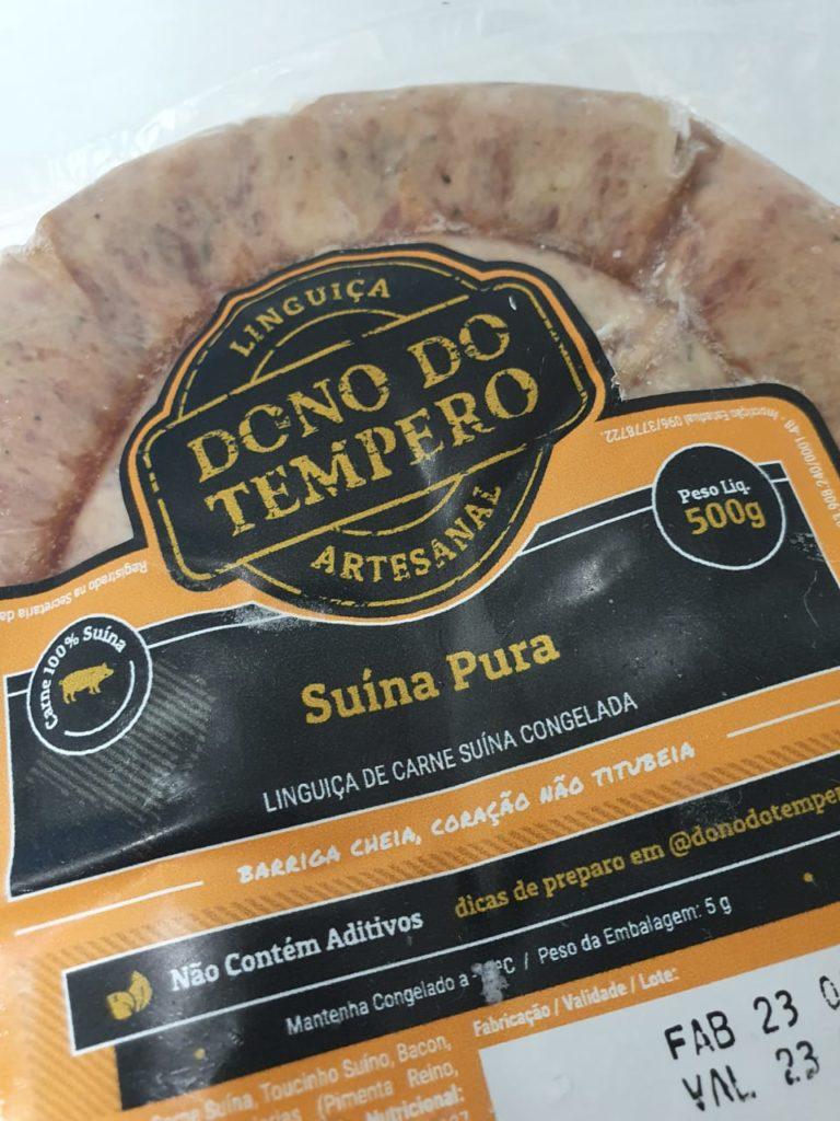 Foto em close de uma embalagem de linguiça suina artesanal da marca dono do tempero com rotulo laranja e preto escrito suina pura, sem aditivos, embalagem de 500 gramas